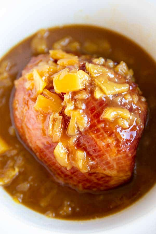 pineapple glazed ham in a white crockpot