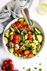 overhead view of white bowl with tomato cucumber avocado salad