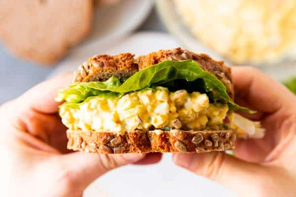 holding an egg salad sandwich with rye bread and lettuce