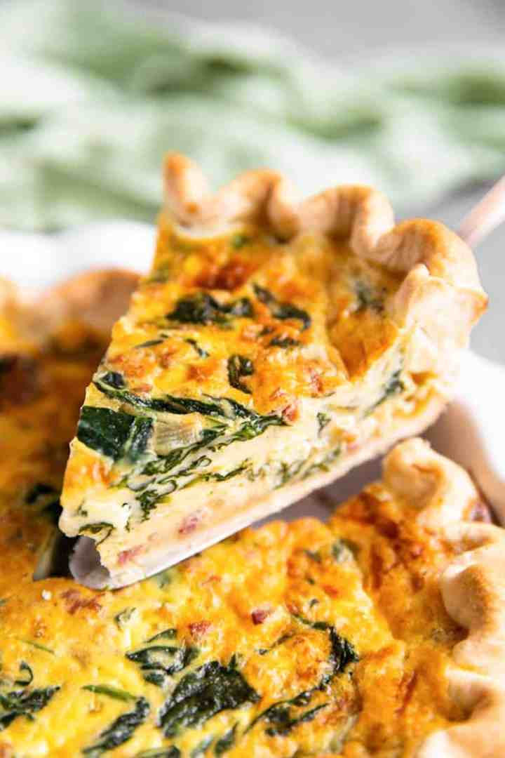 lifting a slice of spinach bacon quiche from the pie dish