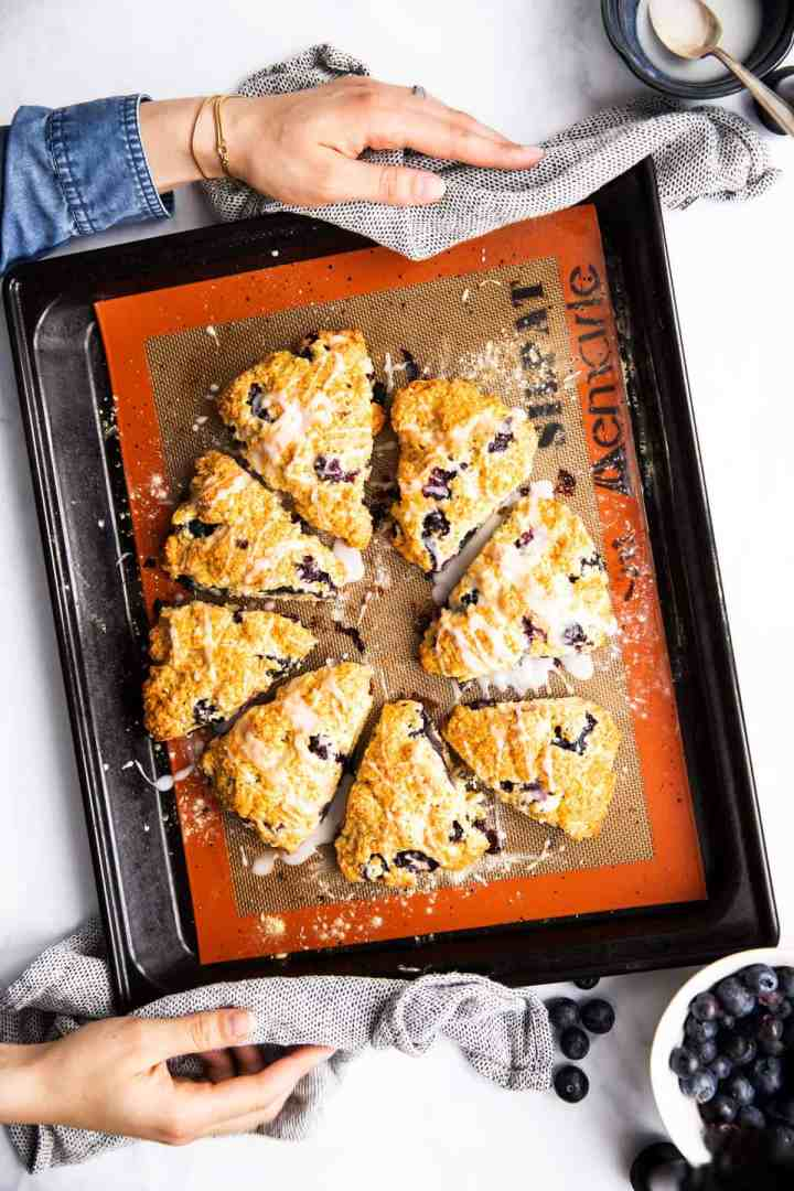 top down view on female hands holding baking sheet with blueberry scones