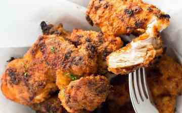 pile of homemade oven fried chicken with a fork stuck in one piece