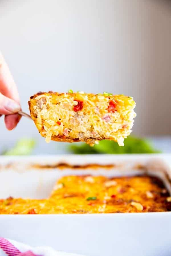 lifting a piece of hashbrown casserole from a baking dish