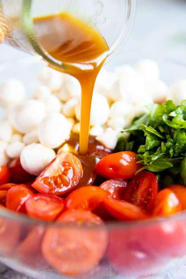 pouring balsamic vinaigrette over caprese cherry tomato salad