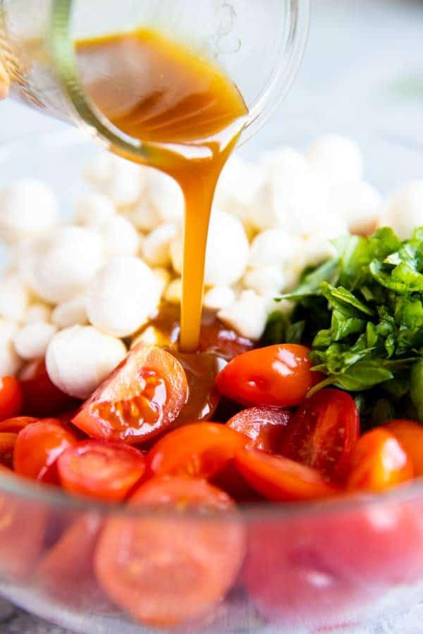 pouring balsamic vinaigrette over caprese cherry tomato salad