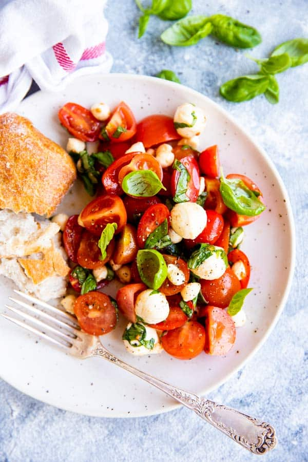 caprese cherry tomato salad on a white plate with crusty bread on the side