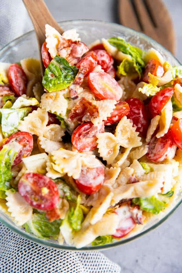 blt pasta salad in a glass bowl with wooden salad tongues