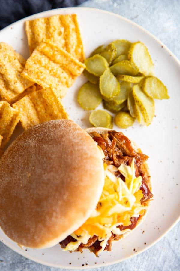 honey bbq pulled pork on a bun, on a white plate with pickles and chips