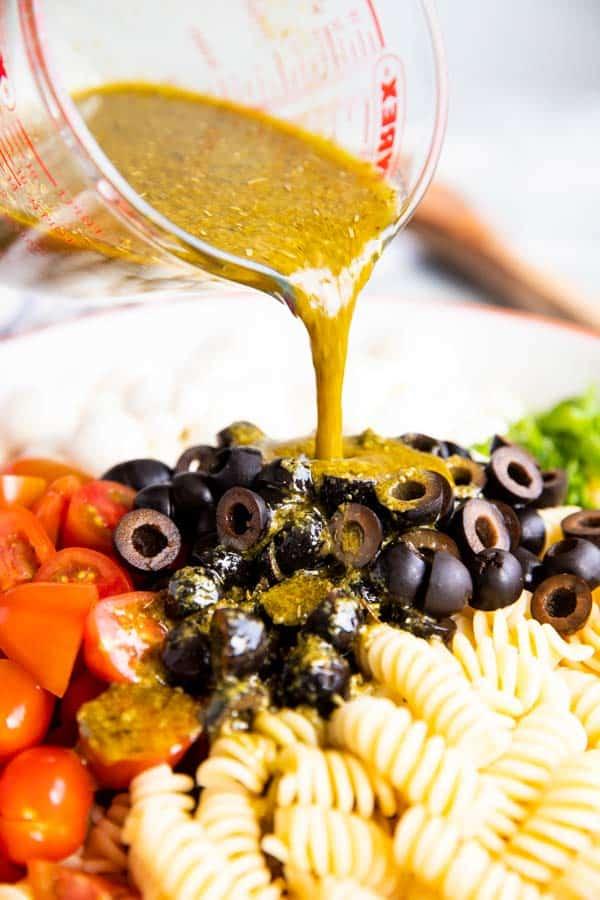 pouring pesto dressing over caprese pasta salad