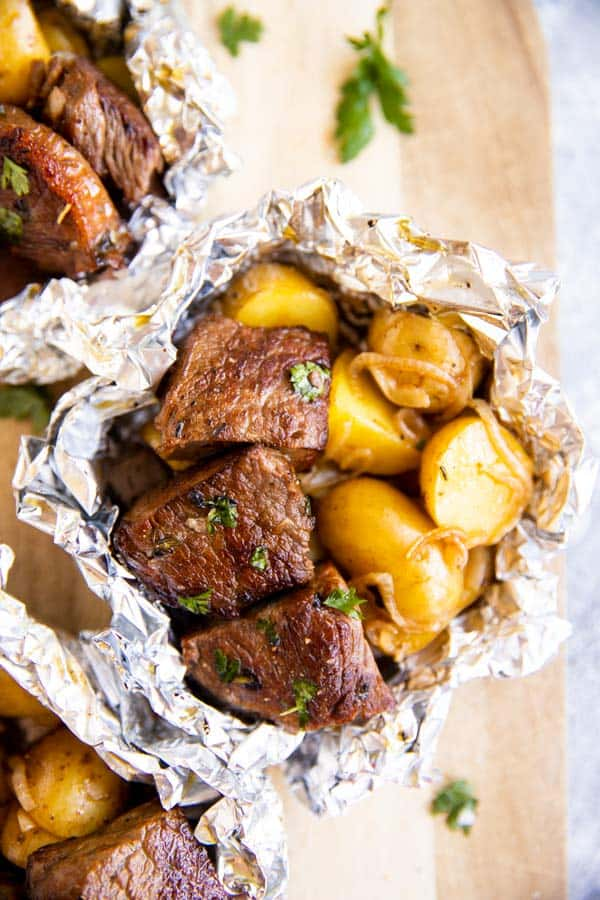 a steak and potato foil packet on a wooden chopping board
