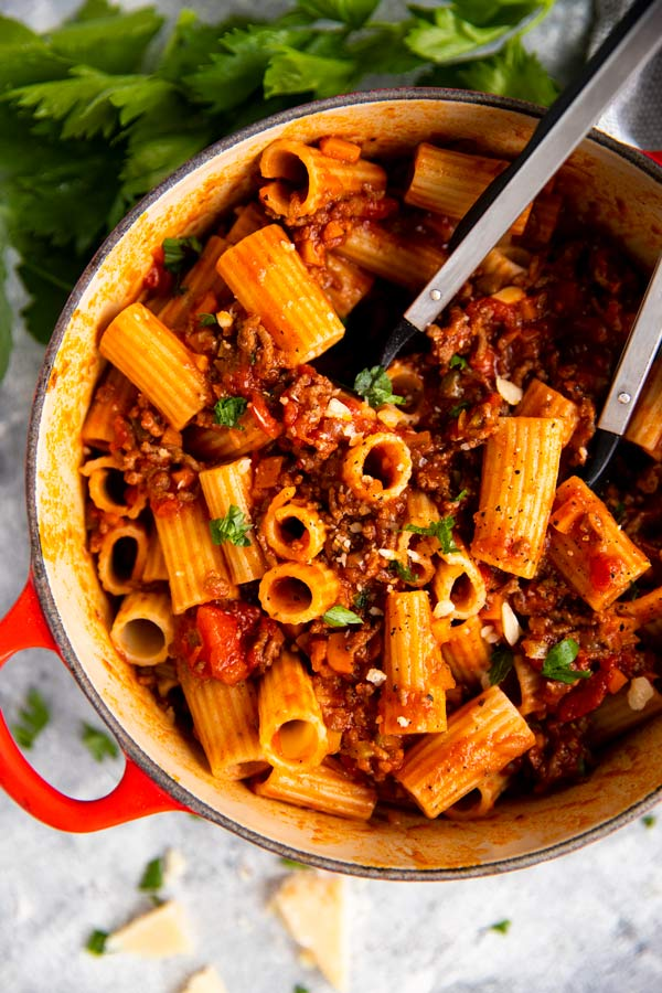 One Pot Rigatoni Bolognese in a Dutch oven with celery, parmesan and serving utensils