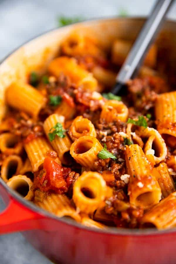 red Dutch oven filled with rigatoni bolognese, from close up