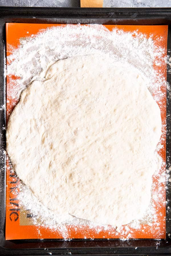 pizza dough rolled out into a circle, on a baking sheet with a silpat mat