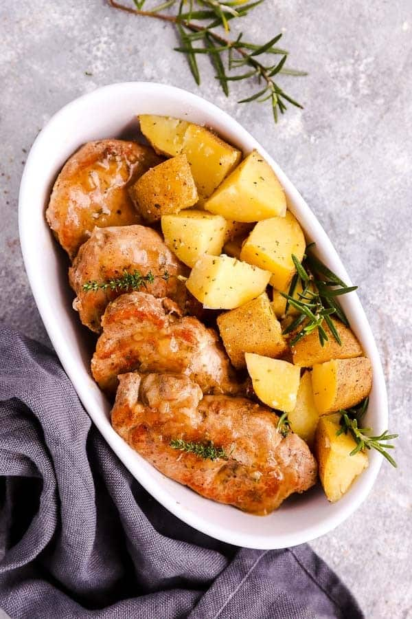 white dish filled with pork chops and rosemary potatoes