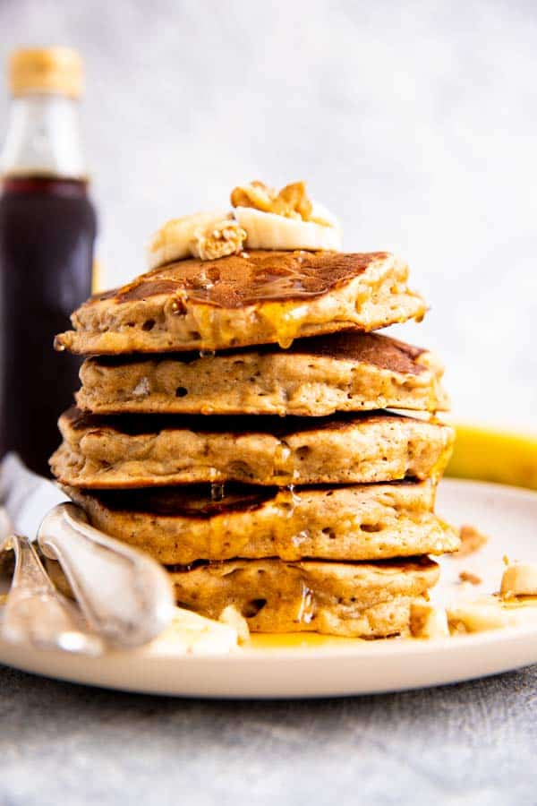 stack of banana pancakes with a bottle of syrup behind it