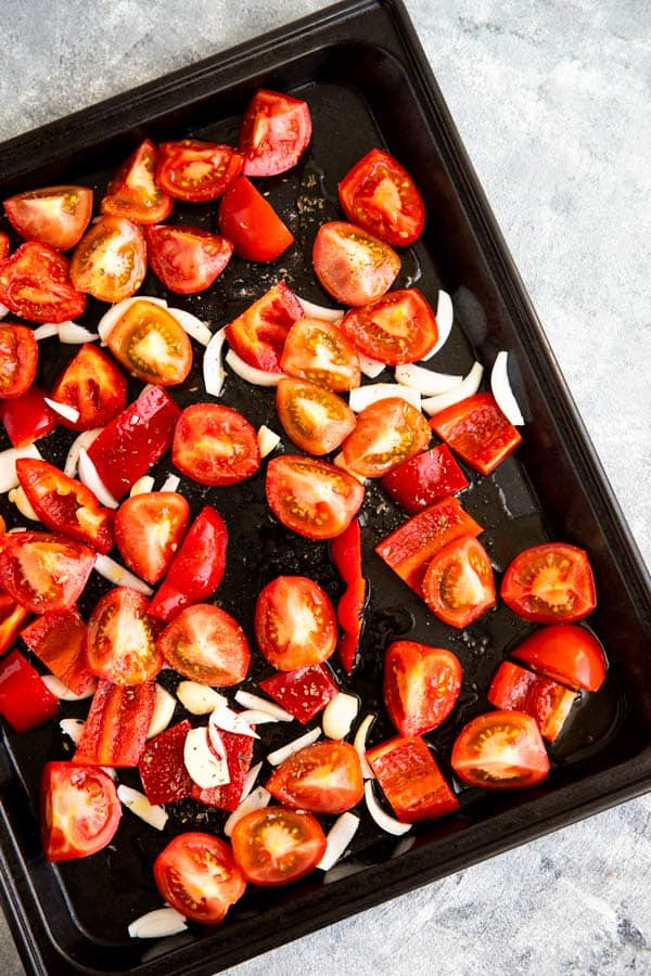 dark baking pan with cut up tomatoes, red pepper, onion and garlic