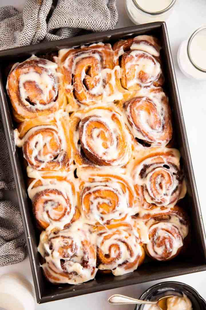 black pan with frosted cinnamon rolls inside