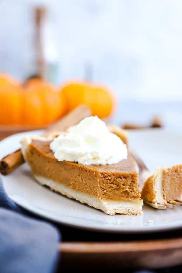slice of pumpkin pie on a white plate with a bite taken out