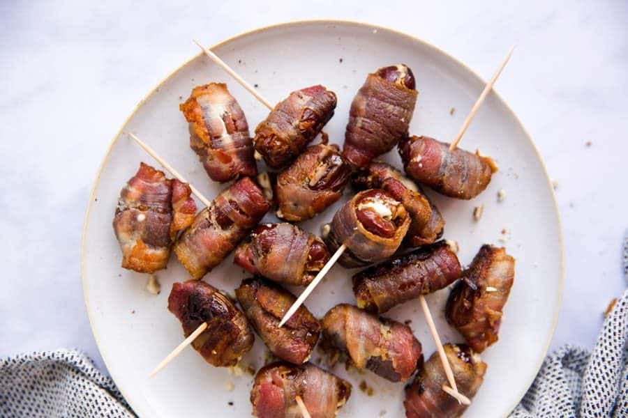 top down view on white plate filled with bacon wrapped dates