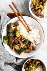overhead view of beef and broccoli in white bowl with chopsticks
