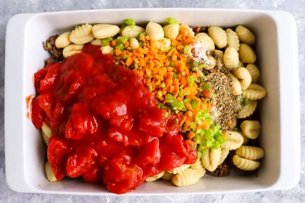 ingredients for gnocchi bake in a white casserole dish