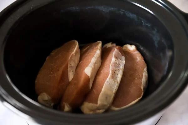 crockpot with raw pork chops inside