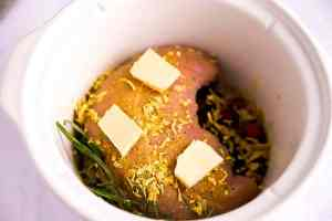 crockpot with cranberries, rosemary and raw turkey breast