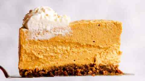 slice of no bake pumpkin cheesecake in front of a light colored wall