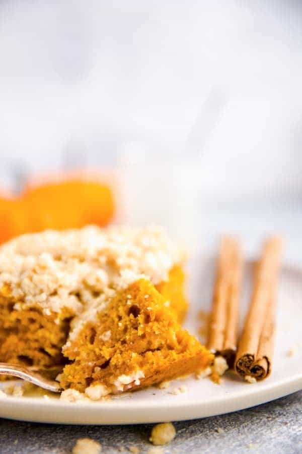 close up photo of a bite taken out of a slice of pumpkin coffee cake