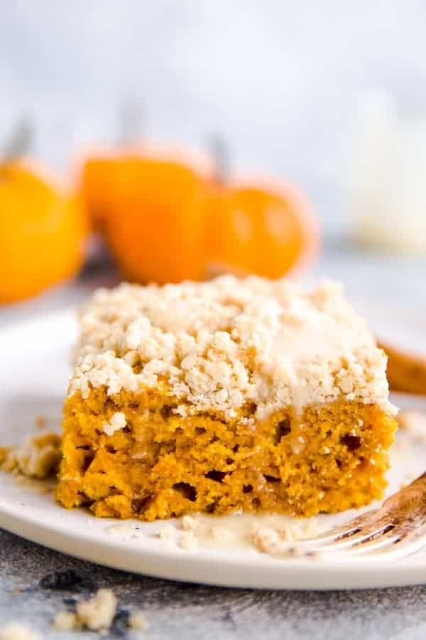 slice of streusel pumpkin coffee cake on a white plate with a few baby pumpkins in the background