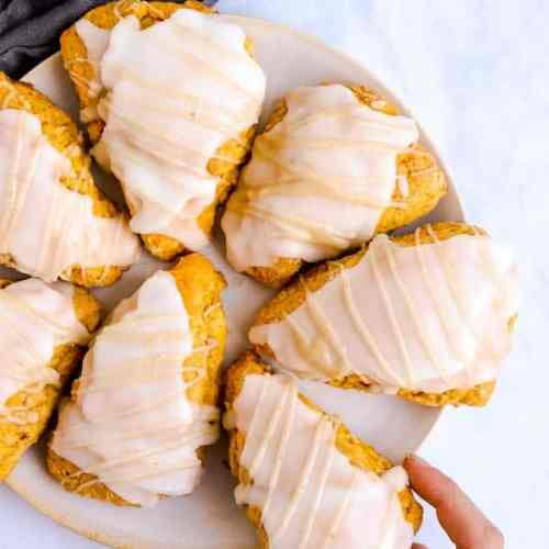 pumpkin scones on a plate with a female hand taking one