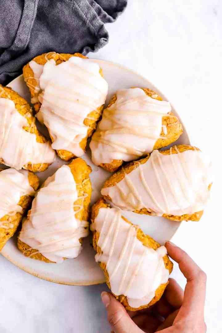 female hand taking pumpkin scone from plate