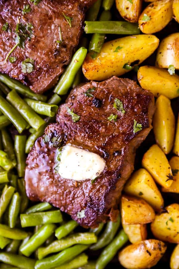 close up photo of a top sirloin steak with butter on a bed of green beans and roasted potatoes