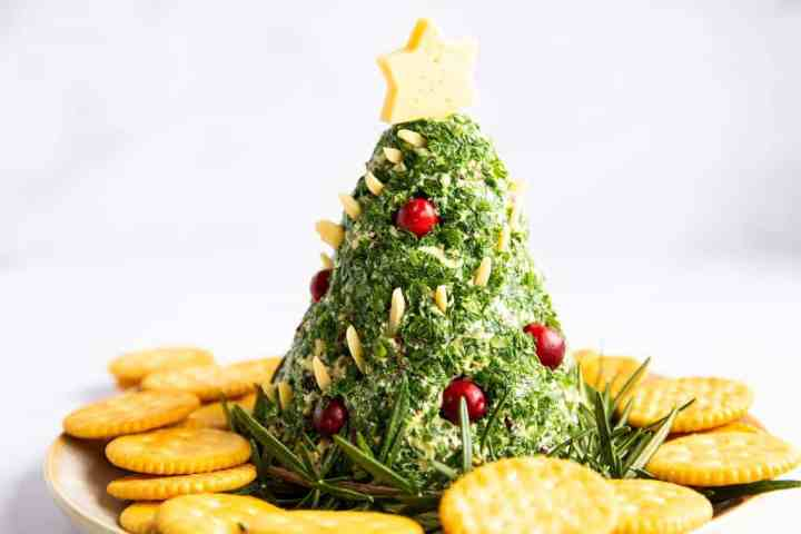 Christmas tree shaped cheeseball on a platter with crackers