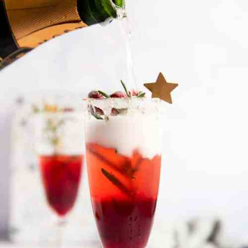 pouring champagne into a flute with cranberry juice