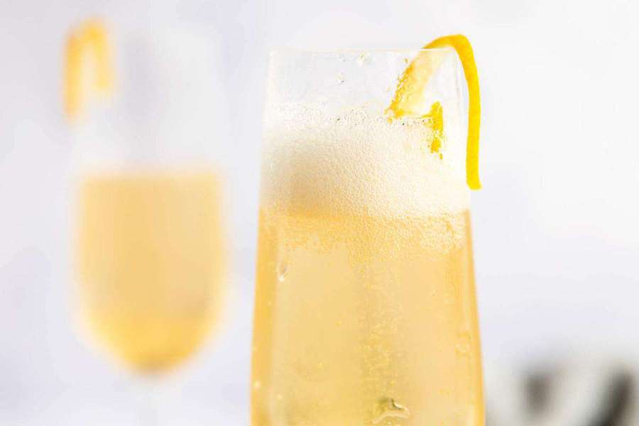 two champagne flutes with elderflower cocktail and lemon peel garnish