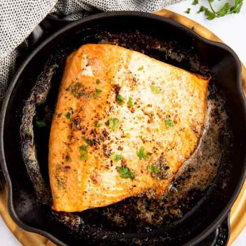 close up photo of a piece of salmon in a skillet