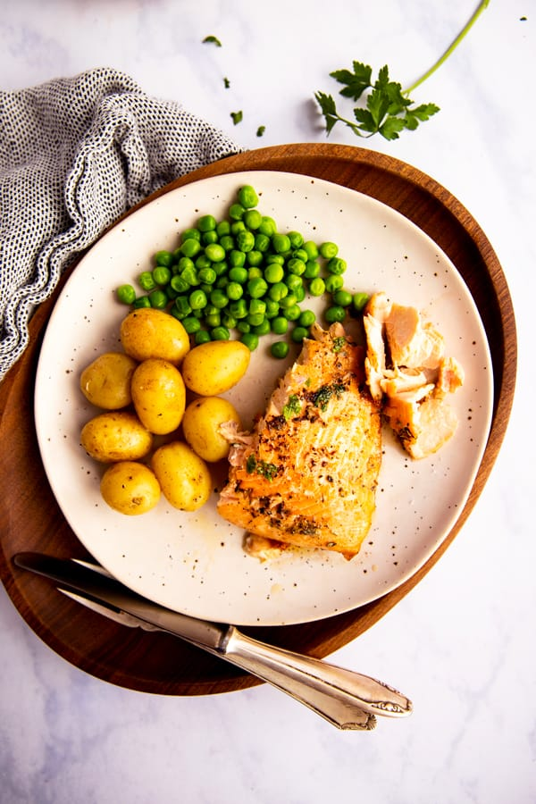 salmon, peas and potatoes on a white plate on top of a wooden platter