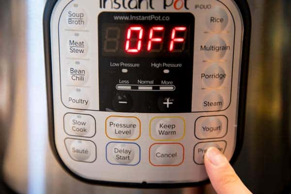 pressing the pressure cooker button on an instant pot