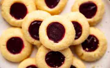 pile of shortbread thumbprint cookies on a cream colored plate
