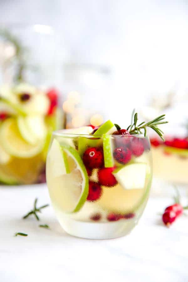 Tumblr with white sangria filled with apple, lime, pomegranate and cranberries