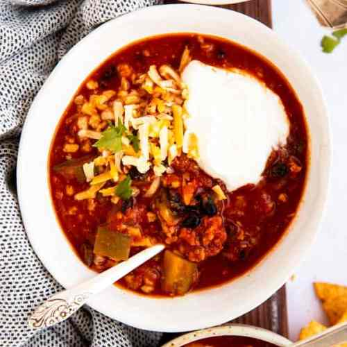 top down view on bowls of turkey chili with sour cream and cheese