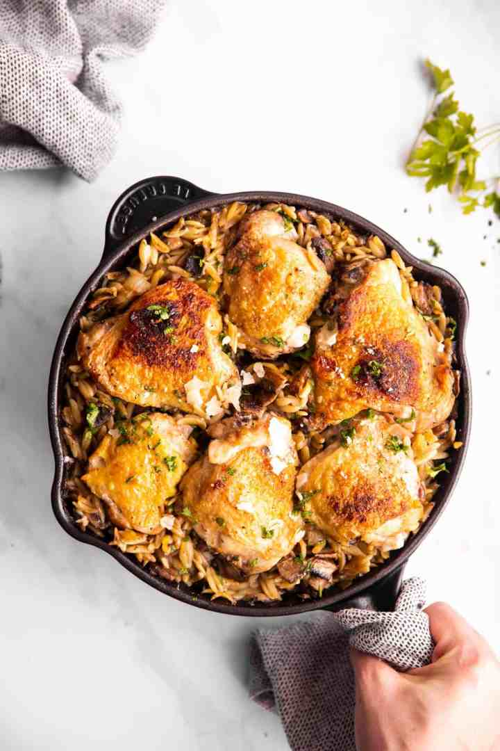 female hand holding skillet with orzo and chicken thighs
