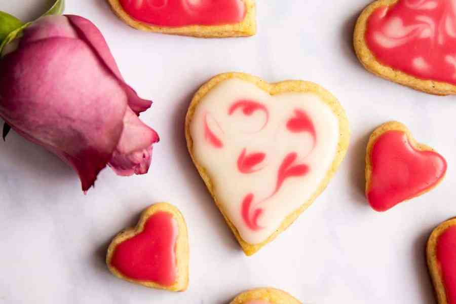 top down view on iced Valentine's Day cookies with pink rose next to them