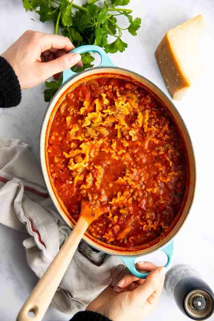 woman holding a pot of lasagna soup