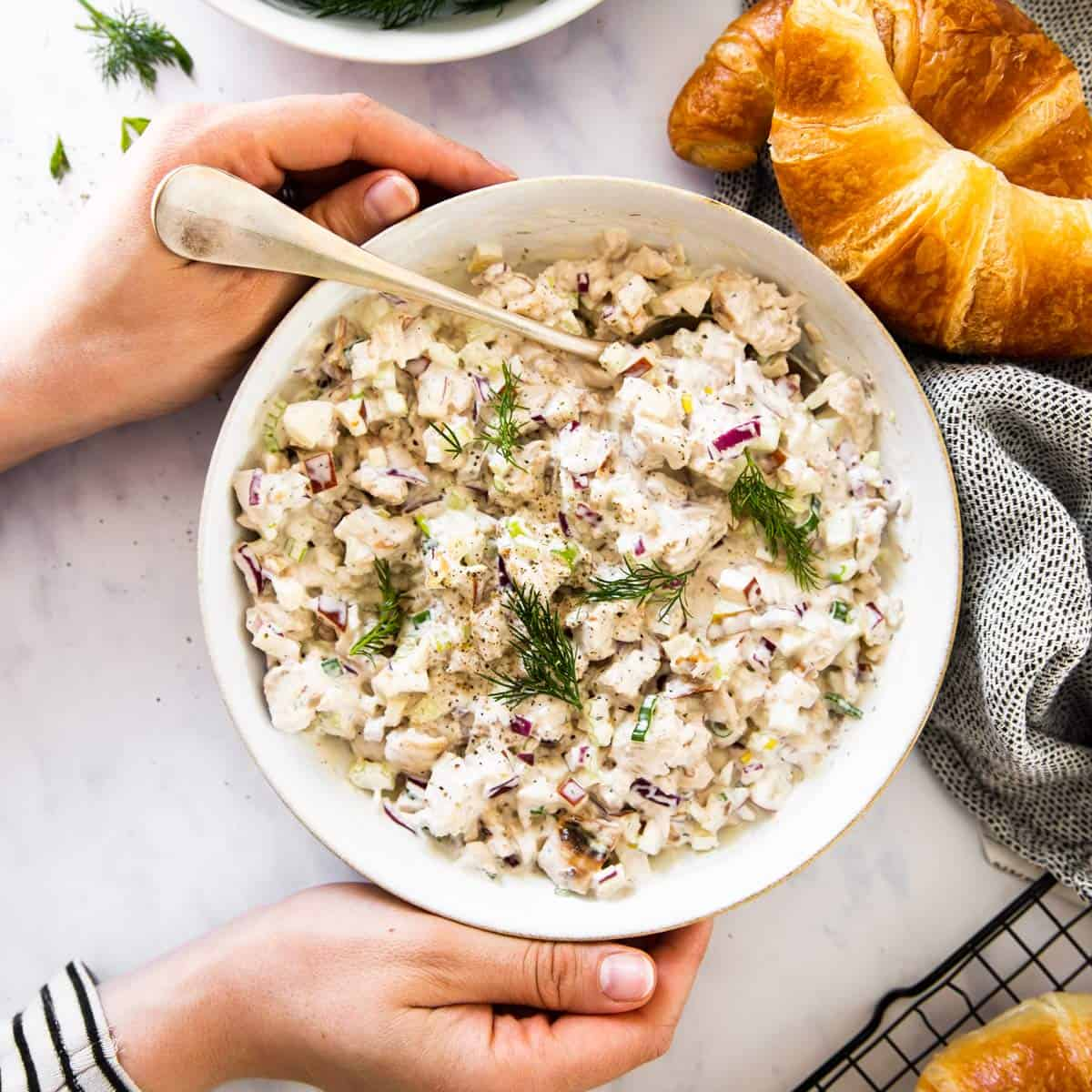top down view on female hands holding white bowl with chicken salad next to croissants