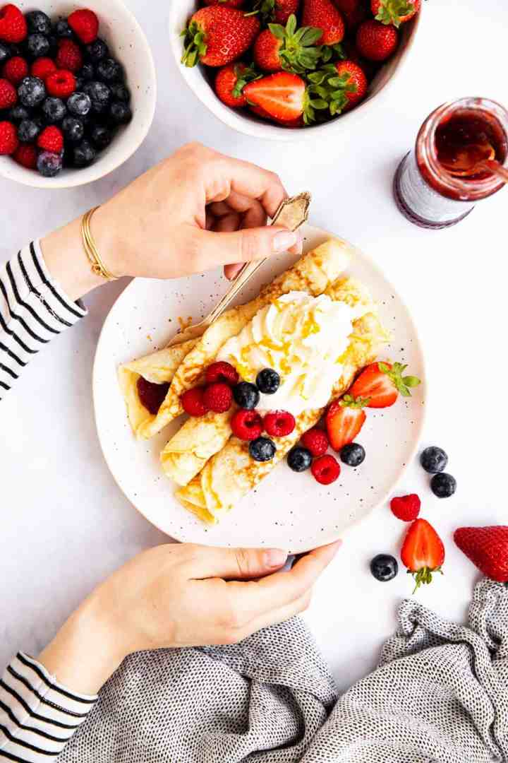 female hands holding plate with crepes