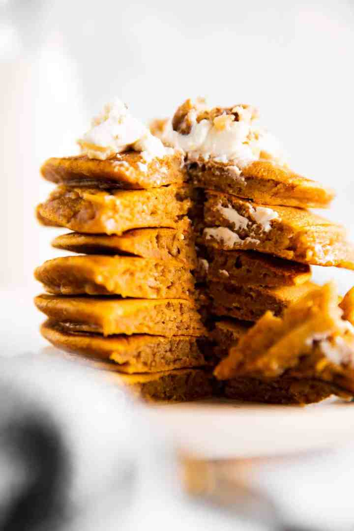 stack of cut open pumpkin pancakes on a white plate