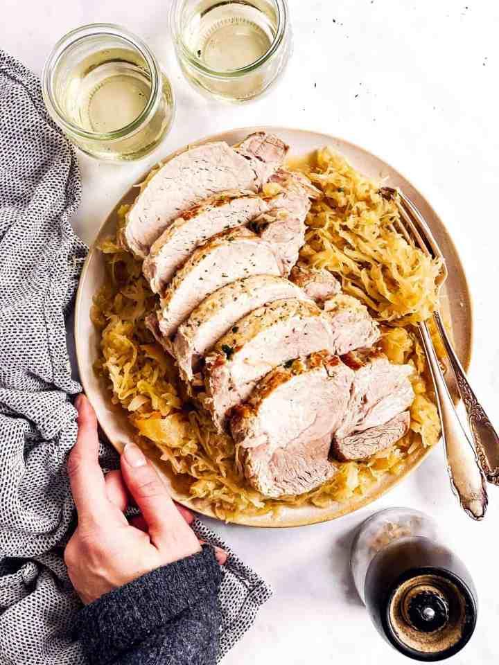 female hand holding platter with sliced pork roast and sauerkraut