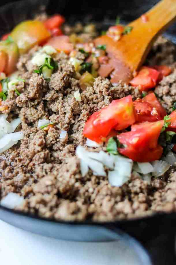 Beef Bolognese Recipe - Savor Thoughts. Tomatoes, garlic, herbs, and onions being added to the beef.